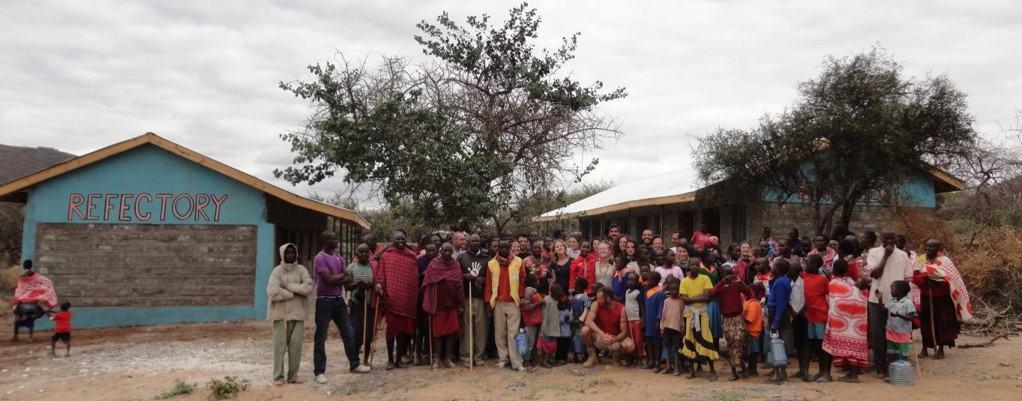 Gruppe von Kindern und Erwachsenen, die den Kindergarten eröffnen.