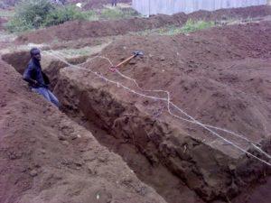 Bild von einem Mann, der einen Graben für den Bau des Kindergartens schaufelt.