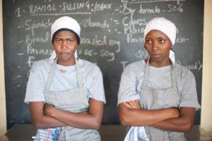 Zwei Kochschülerinnen vor der Tafel mit dem Rezept